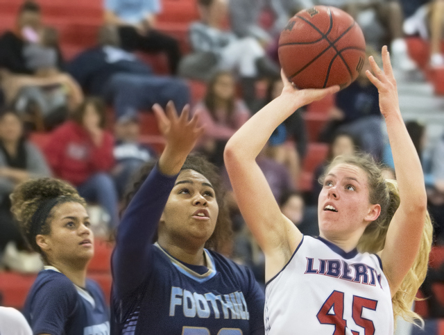 Liberty's Amanda Pemberton (45) drives past Foothills Crystal Davis (30) during the Patriots home matchup with the Falcons on Monday, Jan. 9, 2017, at Liberty High School, in Las Vegas. Benjamin H ...