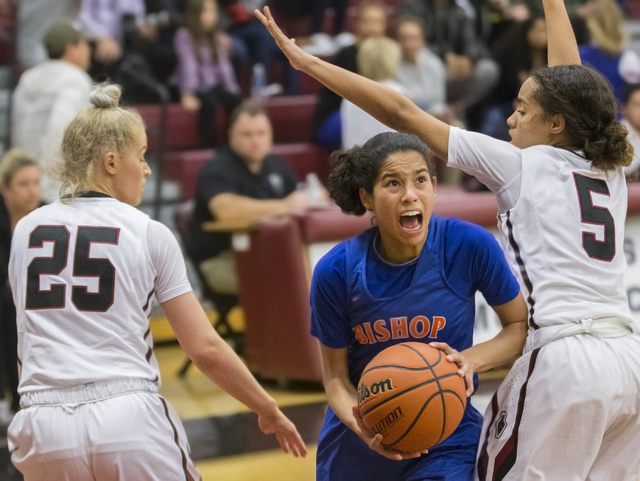 Bishop Gorman's Shaira Young (2) splits Desert Oasis defenders Melissa Simmons (25) and Eliyjah Pricebrooks (5) on the way to the basket during the Gaels road matchup with the Diamondbacks on Tues ...