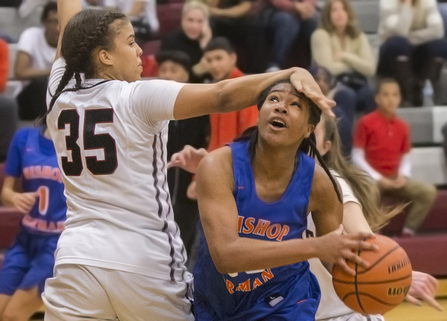 Bishop Gorman's Skylar Jackson (20) gets fouled on the way to the basket by Desert Oasis' Dajaah Lightfoot (35) during the Gaels road matchup with the Diamondbacks on Tuesday, Jan. 10, 2017, at De ...