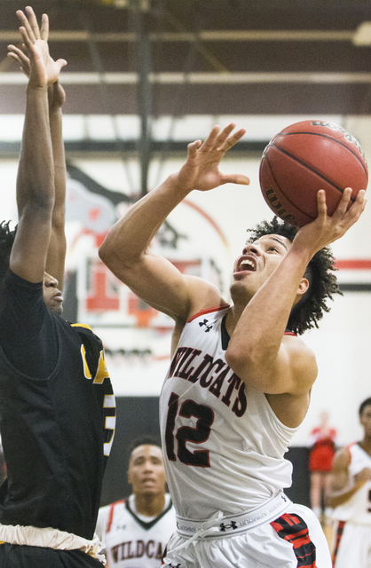 Las Vegas' Donovan Joyner (12) drives to the rim over Clark's Ian Alexander (32) during the Wildcats home matchup with the Chargers on Thursday, Jan. 12, 2017, at Las Vegas High School, in Las Veg ...