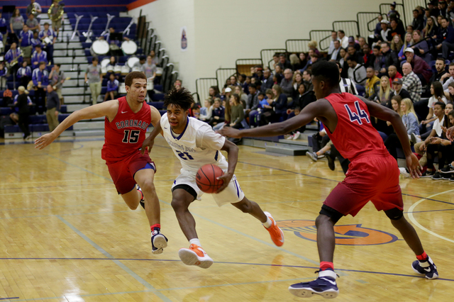 Bishop Gorman's Christian Popoola (21) attempts to push past Coronado's guard Bryce Savoy (15) and forward Taieem Comeaux (44) during a basketball game at Bishop Gorman High School on Tuesday, Dec ...
