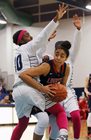 Liberty's Paris Strawther, center, gets tangled up with Canyon Springs defense Dre'una Edwards, left, and Destini Hunter, right, during Wednesday's game. Strawther had 14 points and 12 rebounds in ...