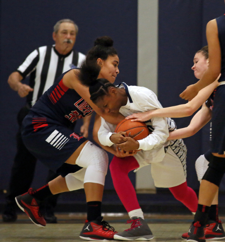Liberty's Paris Strawther, from left, Canyon Springs' Alexia Thrower and Liberty's Kealy Brown struggle over the ball during Wednesday's game. Brown had 20 points, and Strawther scored 14 in Liber ...