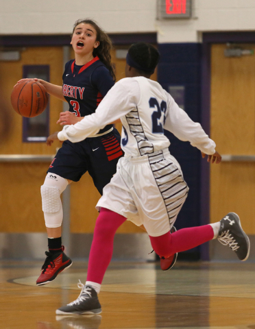 Liberty's CeCe Quintino, left, drives against Canyon Springs' Khelsea Smith during Wednesday's game. Liberty won 58-39. (Ronda Churchill/Las Vegas Review-Journal)