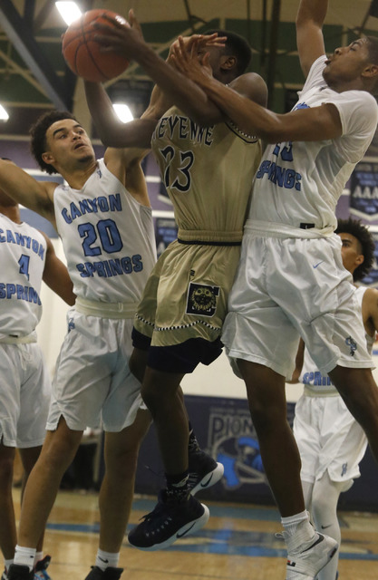 Cheyenne's Dewayne Alexander (23) is fouled hard by Canyon Spring's Joseph Haulcy (20) and Canyon Spring's Elbert Bibbs (23) during a boys basketball game on Friday, Jan. 13, 2017, in Las Vegas. ( ...