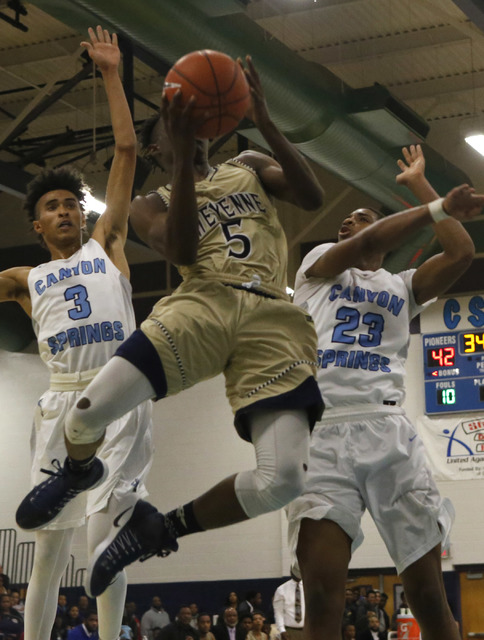 Cheyenne's Kavon Williams (5) shoots against Canyon Spring's Michael Washington (3) and Canyon Spring's Elbert Bibbs (23) during a boys basketball game on Friday, Jan. 13, 2017, in Las Vegas. (Chr ...