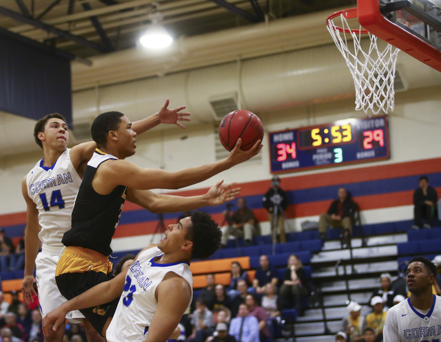 Clark forward Deshawn Wilson (5) goes up for a shot between Bishop Gorman forwards Saxton Howard (14) and Ryan Kiley (23) during a basketball game at Bishop Gorman High School in Las Vegas on Tues ...