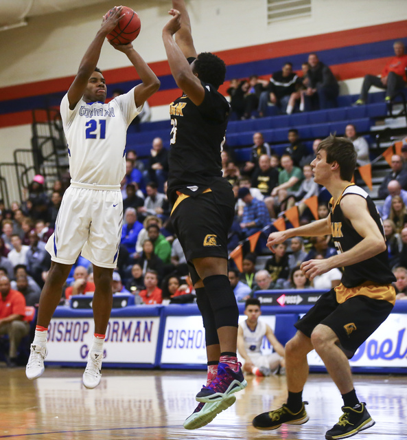 Bishop Gorman guard Christian Popoola (21) shoots over Clark forwards Antwon Jackson (23) and Adam Forbes (30) during a basketball game at Bishop Gorman High School in Las Vegas on Tuesday, Jan. 3 ...