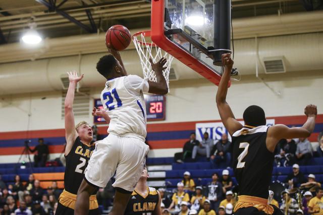 Bishop Gorman guard Christian Popoola (21) goes up for a shot between Clark guards Trey Woodbury (22) and Sedrick Hammond (2) during a basketball game at Bishop Gorman High School in Las Vegas on  ...