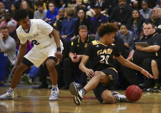 Clark forward Jalen Hill (20) trips up over the ball as Bishop Gorman Jamal Bey (2) looks on during a basketball game at Bishop Gorman High School in Las Vegas on Tuesday, Jan. 31, 2017. Clark won ...