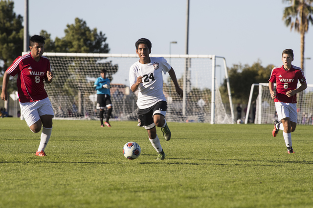 Jair Jaimes-Ponce advances the ball through Valley defenders Andy Gonzales (8) and Fausto Vega (6) during the Sunrise Region boys soccer semifinal game at Bettye Wilson Soccer Complex in Las Vegas ...