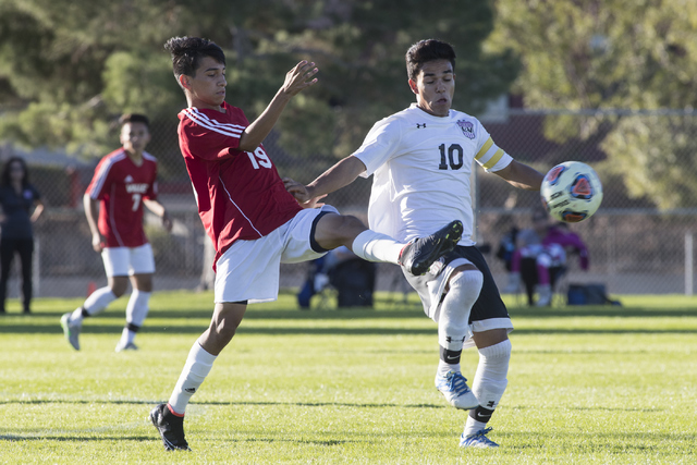 Jose Valles (19), from Valley High School, battles for the ball against Fernando Gomez (10), from Las Vegas High School, during the Sunrise Region boys soccer semifinal game at Bettye Wilson Socce ...