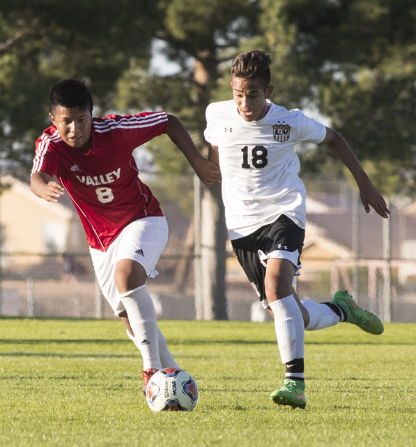 Andy Gonzales (8) from Valley High School, battles for the ball against Roberto Sotomayor (18) from Las Vegas High School, during the Sunrise Region boys soccer semifinal game at Bettye Wilson Soc ...
