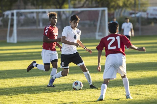 Jonathan Macedo-Castellano (4), from Las Vegas High School, moves the ball up field through Valley High School defenders Josh Cloyd (9) and Sergio Ortiz (21) during the Sunrise Region boys soccer  ...