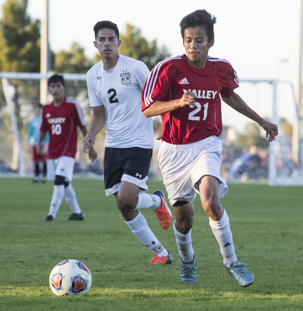 Sergio Ortiz (21), from Valley High School, battles for the ball against Isac Nolasco (2), from Las Vegas High School, during the Sunrise Region boys soccer semifinal game at Bettye Wilson Soccer  ...