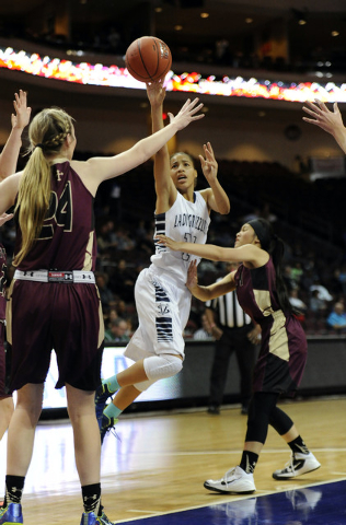 Spring Valley forward Kayla Harris attempts a shot as Faith Lutheran guard Madison Bocobo defends during the second half of the Division I-A girls state championship game at the Orleans Arena in L ...