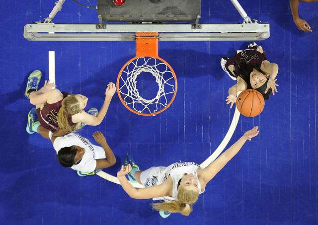 Faith Lutheran guard Madison Bocobo, left, pulls down a Spring Valley rebound in front of guard Jessica Rafay, middle, during the second half of the Division I-A girls state championship game at t ...