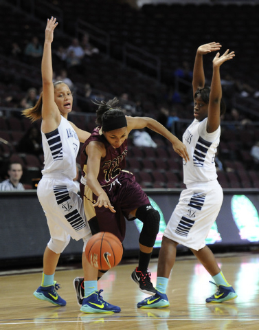 Faith Lutheran guard Haley Vinson (12) splits through Spring Valley guards Essence Booker, left, and Shantriel Thompson in the first half of the Division I-A girls state championship game at the O ...