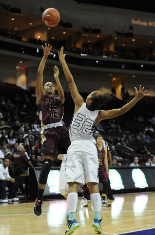 Faith Lutheran guard Haley Vinson (12) makes a field goal attempt as Spring Valley Lynnae Wilds (32) defends in the first half of the Division I-A girls state championship game at the Orleans Aren ...