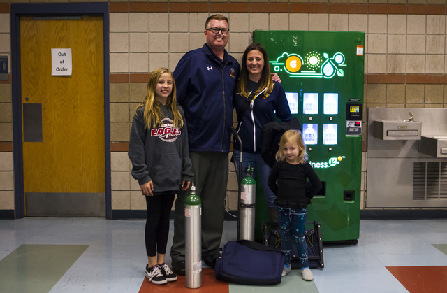 Boulder City girls basketball coach Paul Dosch poses with, from left, Alexis Farrar, 11, fiancé Katie, and daughter Harper, 4, after a basketball game at Del Sol High School in Las Vegas on Tuesd ...