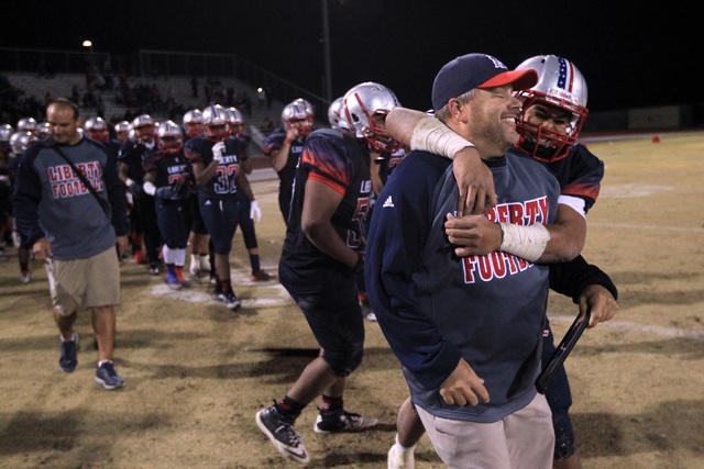 Liberty head coach Richard Muraco gets a hug from Josh Bernard lee after they defeated Green Valley Friday, Nov. 7, 2014 at Liberty High School. Liberty won 28-14. (Sam Morris/Las Vegas Review-Jou ...