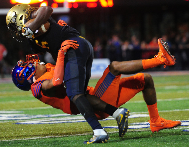 Bishop Gorman safety Greg Francis, bottom, tackles St. Thomas Aguinas, Fla. wide receiver Jordan Merrell in the first half of their prep football game at Bishop Gorman High School in Las Vegas Fri ...