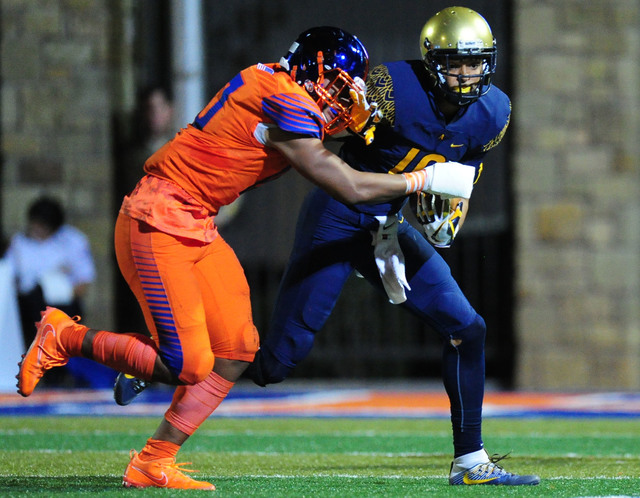 St. Thomas Aguinas, Fla.  Trevon Grimes grabs the facemask of Bishop Gorman offensive linebacker Palaie Gaoteote while rushing in the first half of their prep football game at Bishop Gorman High S ...