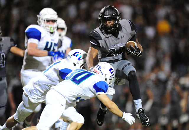 Green Valley linebacker Avery Fleharty, right, and Ty Rivera tackle Palo Verde running back Terrill Jimerson in the first half of their prep football game at Palo Verde  High School in Las Vegas F ...