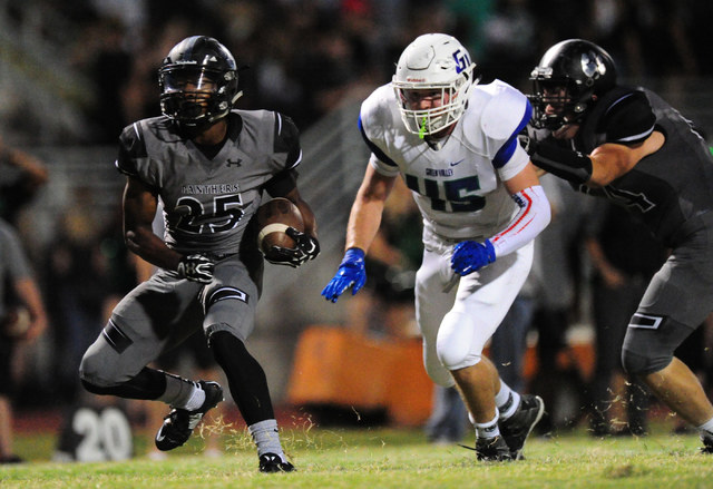 Palo Verde running back Terrill Jimerson looks for running room as Green Valley linebacker Brock Hershberger closes in during the first half of their prep football game at Palo Verde  High School  ...