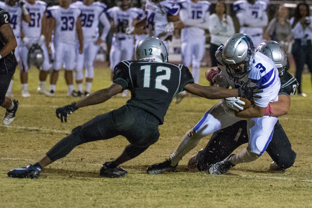 Silverado wide receiver Anthony Bugay (3) is tackled by Green Valley defenders Israel Robinson (12) and Eric Faber (34) during the first half at Green Valley High School in Henderson on Friday, Oc ...