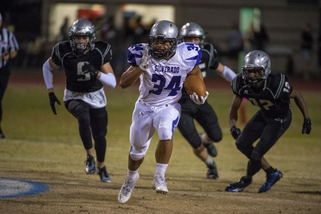 Silverado running back Keikiokalani Misipeka (34) runs with the ball as Green Valley defenders chase during the first half at Green Valley High School in Henderson on Friday, Oct. 7, 2016. Joshua  ...
