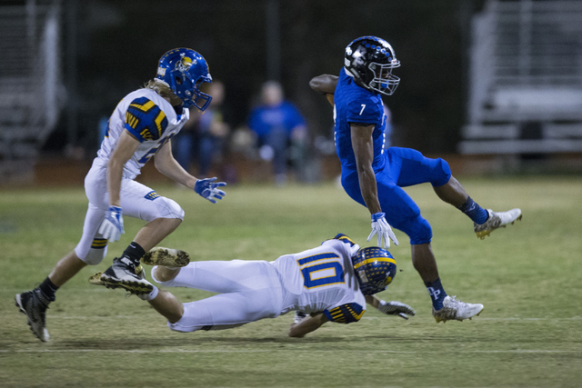 Desert Pines running back Isaiah Morris (7) leaps over a tackle attempt by Moapa Valley's Dayton Wolfley in their state quarterfinal football game at Desert Pines High School on Friday, Nov. 4, 20 ...