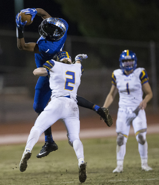 Desert Pines wide receiver Tony Fields (1) makes a catch as is is tackled by Moapa Valley's Jacob Leavitt (2) in their state quarterfinal football game at Desert Pines High School on Friday, Nov.  ...