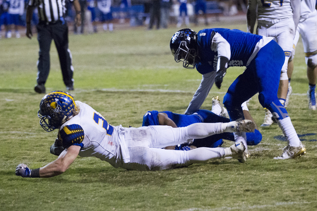 Moapa Valley's Jacob Leavitt (2) is tackled in the end zone for a touchdown against Desert Pines in their state quarterfinal football  game at Desert Pines High School on Friday, Nov. 4, 2016, in  ...
