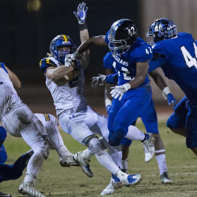 Moapa Valley's Jacob Leavitt (2) is tackled by Desert Pines' Jautae Collins (42) in their state quarterfinal football  game at Desert Pines High School on Friday, Nov. 4, 2016, in Las Vegas. Deser ...