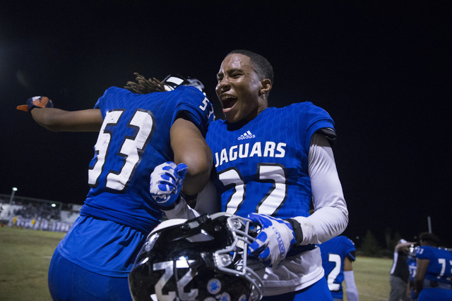 Desert Pines's Lorenzo Brown (53) and Andrew William (22) celebrate their win against Moapa Valley in their state quarterfinal football game at Desert Pines High School on Friday, Nov. 4, 2016, in ...