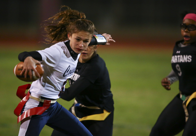 Coronado's Caitlin Shannon (9) evades Cimarron-Memorial defenders while running the ball during the Class 4A state championship flag football game at Cimarron-Memorial High School on Wednesday, Fe ...