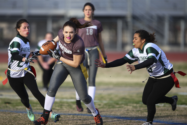 Cimarron-Memorial's Logan DeLong (4) runs the ball between Palo Verde's Jordan Schnitz (24) and Madison Hearn (80) during the Sunset Region flag football championship game at Green Valley High Sch ...