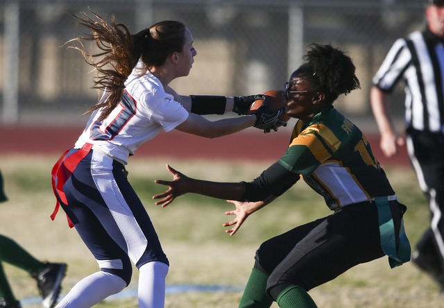 Coronado's Trinity Rhoades (11) comes into contact with a Rancho player during a flag football game at Green Valley High School in Henderson on Tuesday, Feb. 14, 2017. Coronado won 41-6. (Chase St ...