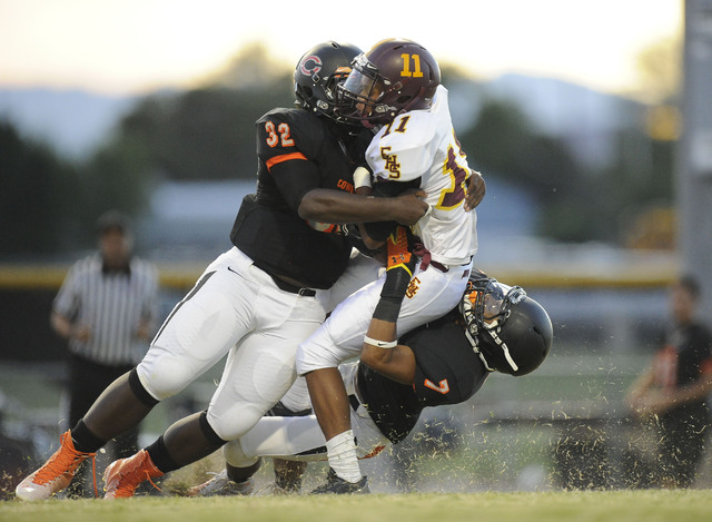Chaparral linebacker Antwain Allen (32) and defensive back Malachi Miles (7) tackle Eldorado wide receiver Demoreyah Holmes (7) in the first quarter on Friday. (Josh Holmberg/Las Vegas Review-Journal)