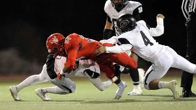 Palo Verde defensive back Graeson Vereen (1) and Palo Verde defensive back Darrion Finn (4) tackle Arbor View running back Herman Gray (34) in the first quarter on Friday. Gray rushed for 136 yard ...