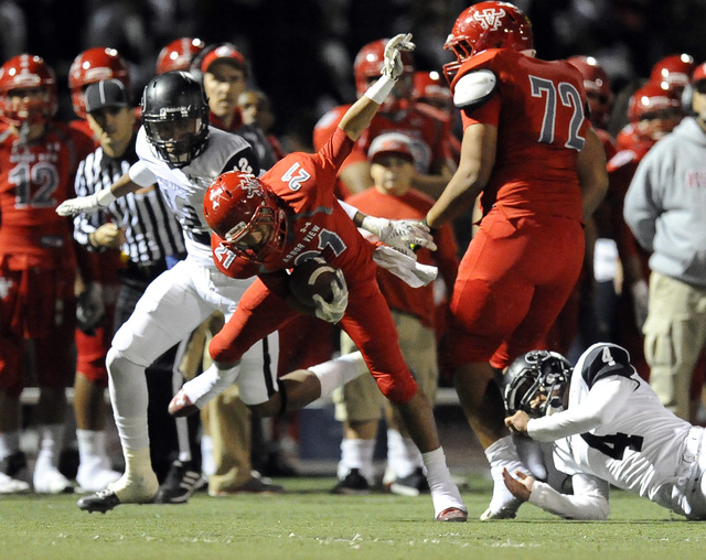 Palo Verde defensive back Devion Clayton (12) and defensive back Darrion Finn (4) trip up Arbor View running back Charles Louch (21) in the first quarter on Friday. Louch rushed for 103 yards and  ...