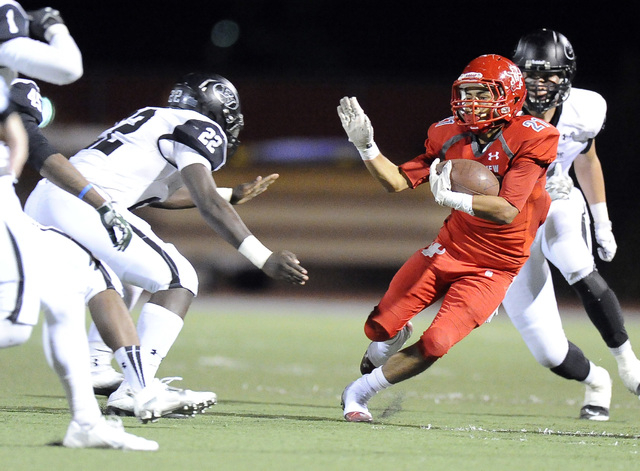 Arbor View center running back Charles Louch (21) looks for running room as Palo Verde linebacker Chauntez Thomas (22) closes on Friday. Louch rushed for 103 yards and a touchdown in a 24-7 win. ( ...