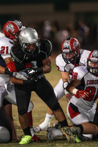 Green Valley's Brenan Adams (3) holds onto the ball while being tackled by Coronado's Darrien Rivera (21) at a football game at Green Valley High School in Henderson Friday, Oct. 10, 2014. (Donavo ...
