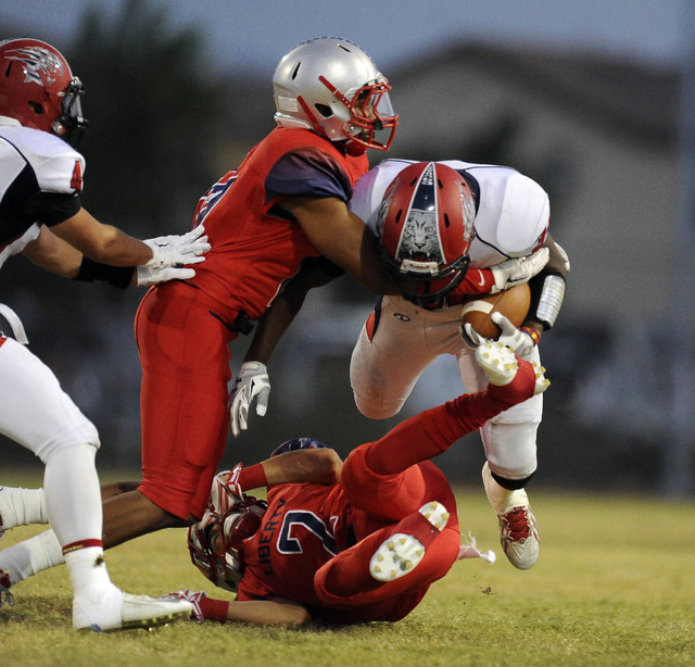 Liberty defensive end Rudy Bukassa, left, and defensive back Ethan Dedeaux (2) tackle Coronado running back Jordan Patterson in the first quarter on Friday. (Josh Holmberg/Las Vegas Review-Journal)