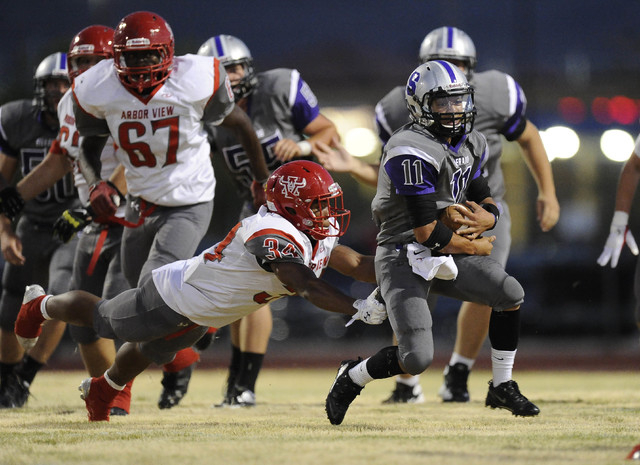 Silverado running back Jarrett Alipio (11) breaks the tackle of Arbor View linebacker Herman Gray (34) in the first quarter on Friday. (Josh Holmberg/Las Vegas Review-Journal)