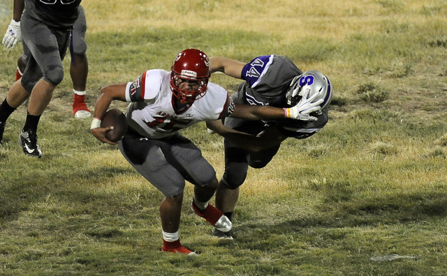 Arbor View quarterback Bryce Poster breaks the tackle of Silverado linebacker Garrett Chanice (44) in the second quarter on Friday. (Josh Holmberg/Las Vegas Review-Journal)