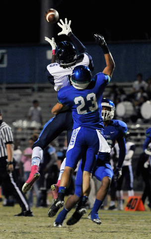 Canyon Springs' Kujuan Casey, grabs a reception over Green Valley's Albert Lake on Friday. (David Becker/Las Vegas Review-Journal)
