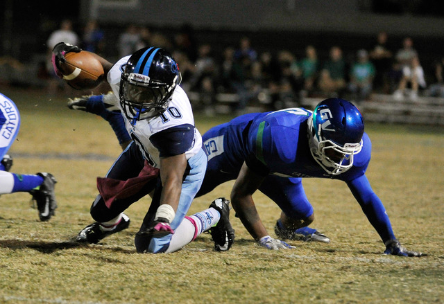 Canyon Springs' Jerrod Blackwell (10) reaches for extra yardage against Green Valley's David Otuafi on Friday. (David Becker/Las Vegas Review-Journal)