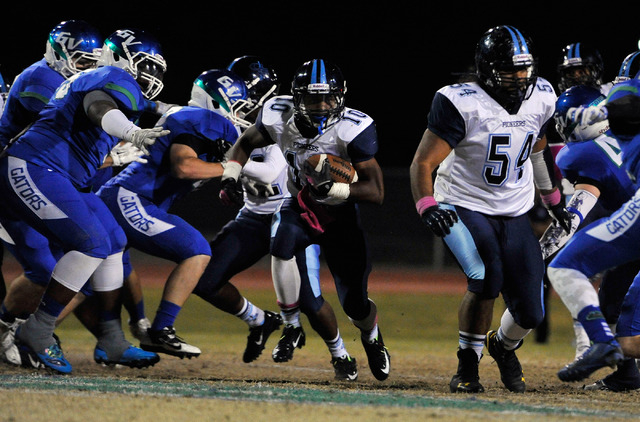 Canyon Springs' Jerrod Blackwell (10) finds a hole as he carries the ball against Green Valley on Friday. (David Becker/Las Vegas Review-Journal)